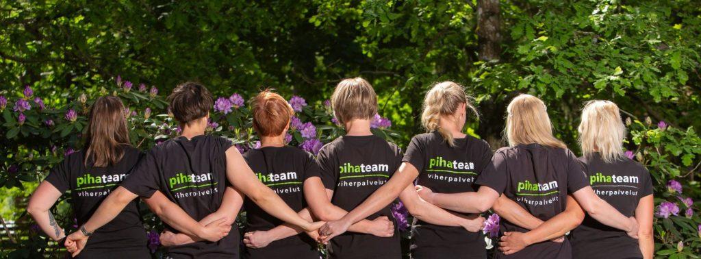 Puutarhurit yhteiskuvassa selin kameraan. Puutarhurit pitävät toisiaan käsistä selkien takana päällään Pihateam -logollinen paita.